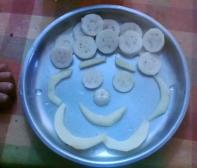 Slice banana and cut apple into thin sections. Arrange in a happy face! Chetana K, Bangalore.