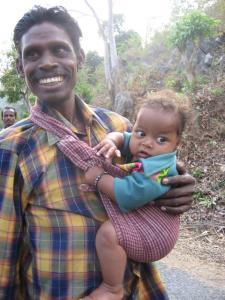 Father carries baby in sling while walking home from the market in rural Orissa.