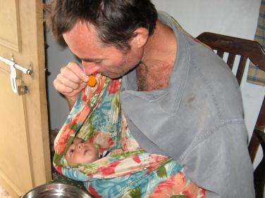 Peter eats while cradling Swandana in her sling.