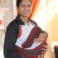 Sunita carries Anika in cradle position in the sling.