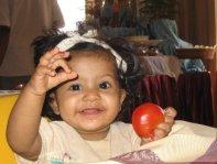 8 month old Khiyali bites a tomato.