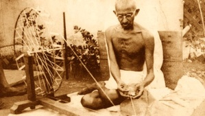 Gandhi spinning cotton on the charkha. Image: WIkimedia Commons.