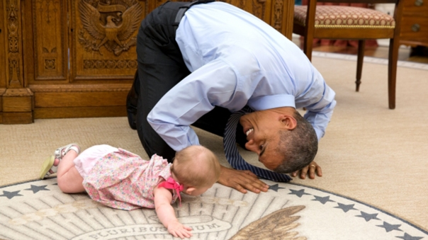 Obama on the floor playing with a baby.